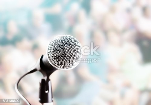 istock Brightly lit microphone in front of defocused audience 625136600