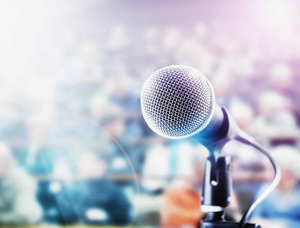 brightly lit microphone in front of out-of-focus audience - oratore pubblico foto e immagini stock