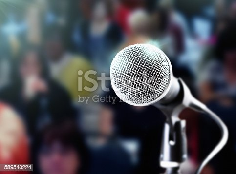 istock Brightly lit microphone with dark, defocused audience in the background 589540224