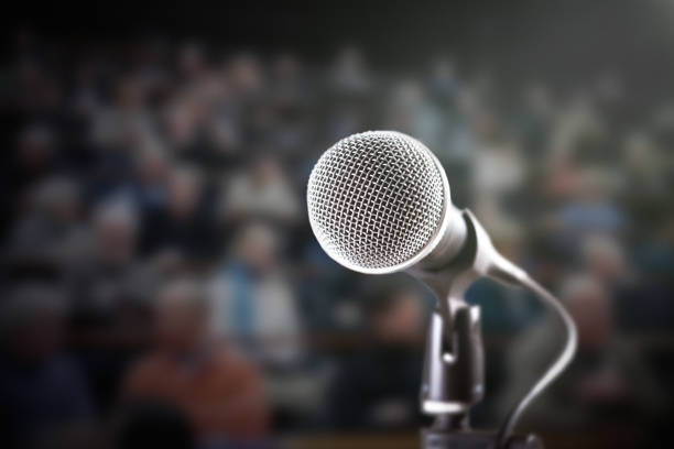 Brightly lit microphone with dark, defocussed audience in background stock photo