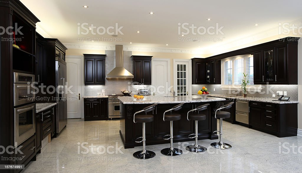 A brightly lit modern kitchen with bar stools royalty-free stock photo