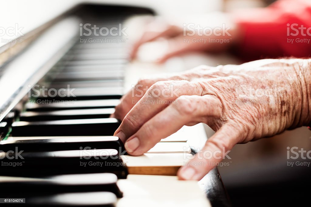 Brightly lit wrinkly old hands playing the piano - foto de stock