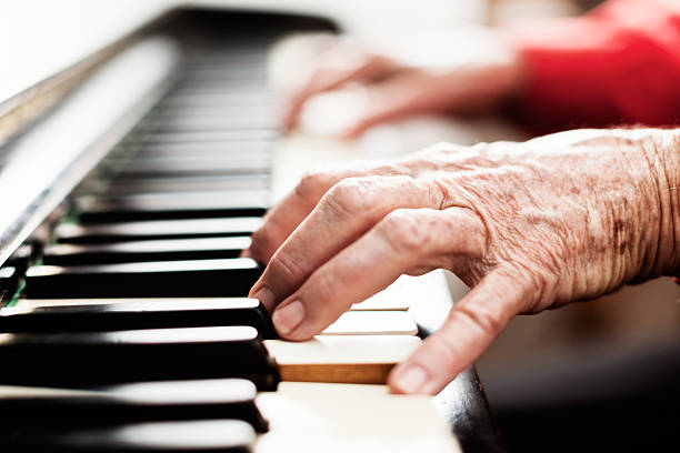 Brightly lit wrinkly old hands playing the piano stock photo