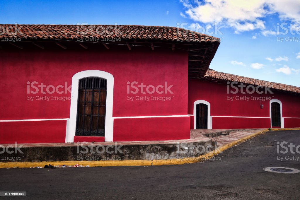 Brightly painted buildings line a winding street in the colonial city...
