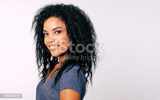 910856488 istock photo Brightness. Portrait of magnificent African American woman with dark wavy hair standing in profile and looking to the camera with cheerful smile. 1180642161