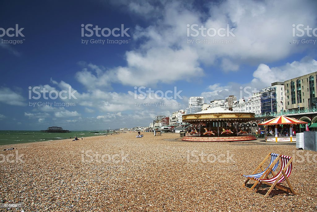 Brighton Beach on cloudy day with amusement park rides stock photo