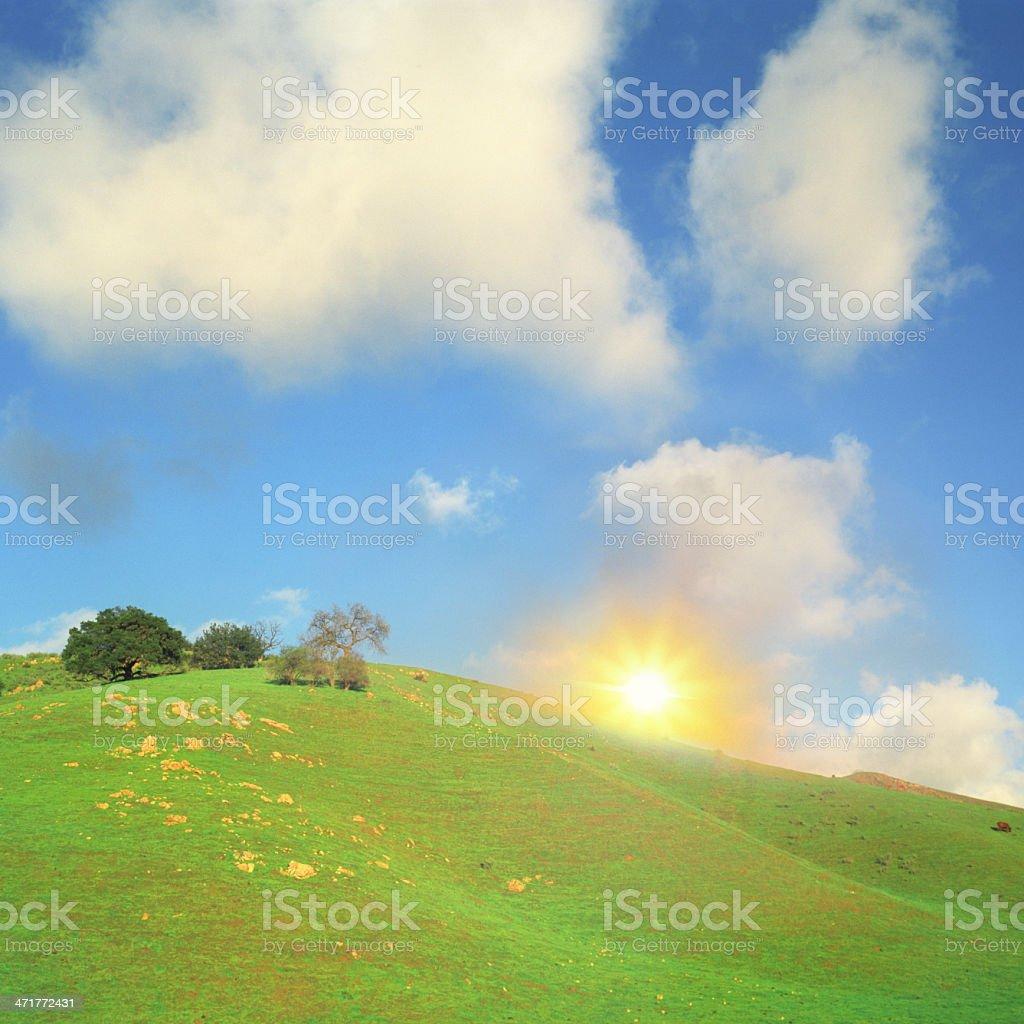 Briliant Sun Rises behind Green Hill royalty-free stock photo
