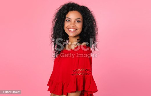 857924506 istock photo Brilliance. Marvelous African ethnic woman in a red blouse is posing in semi-profile, looking right at the camera with a charming smile. 1182103428