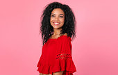 istock Brilliance. Marvelous African ethnic woman in a red blouse is posing in semi-profile, looking right at the camera with a charming smile. 1182103428