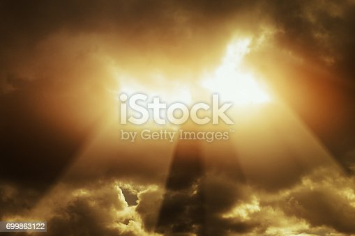 From a dark, stormy sky, rays of light shine down through a break in the clouds., looking like the Gates of Heaven.