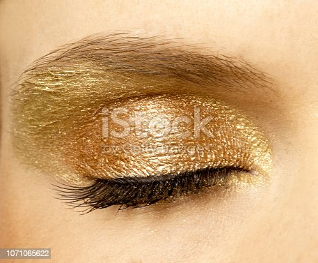 brilliant gold and shiny  eyes shadow close-up with closed eye