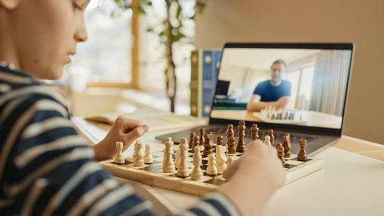 Brilliant Little Boy Playing Chess with His Distant Relative or Uncle, Uses Laptop for Video Call. Remote Online Education, E-Education, Communication with Family, Homeschooling.