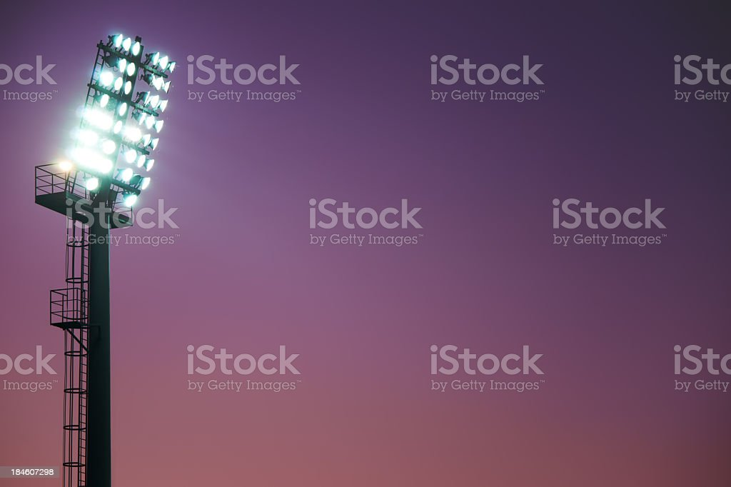 Brilliant stadium lights side view cast in lilac evening sky royalty-free stock photo