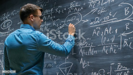 istock Brilliant Young Mathematician Approaches Big Blackboard and Finishes writing Sophisticated Mathematical Formula/ Equation. 963424238