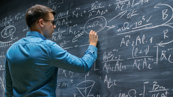 Brilliant Young Mathematician Approaches Big Blackboard And Finishes Writing Sophisticated Mathematical Formula Equation Stock Photo - Download Image Now