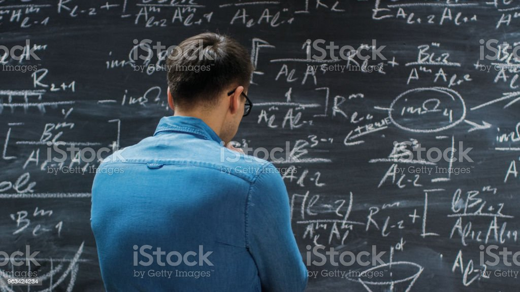 Brilliant Young Mathematician Approaches Big Blackboard and Thinking about Sophisticated Mathematical Formula/ Equation. - Zbiór zdjęć royalty-free (Analizować)