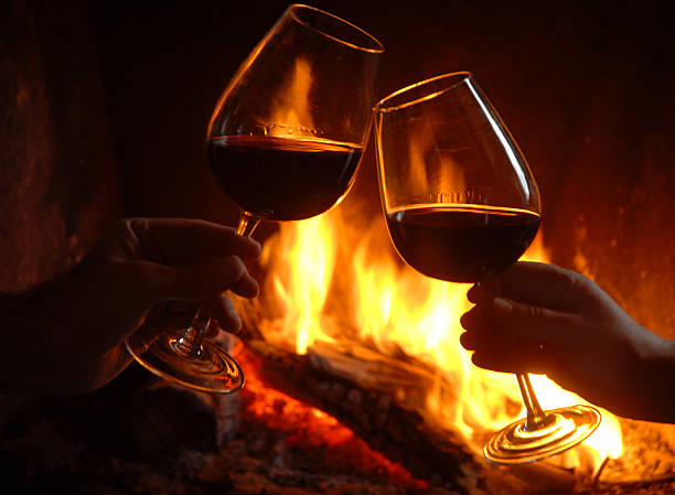 Brindis Gands holdinf reed wine cups, fireplace background. log fire stock pictures, royalty-free photos & images