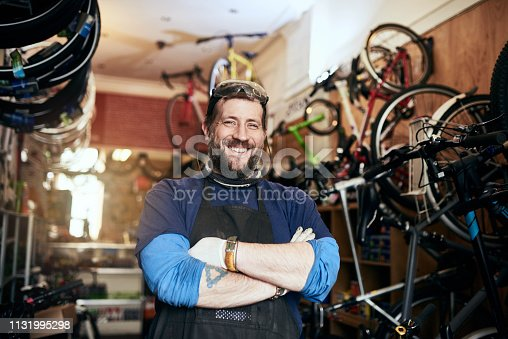 Shot of a handsome man working in his self-owned bicycle workshop