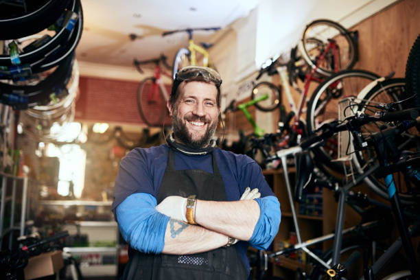Bring all your bike repairs and maintenance jobs to me Shot of a handsome man working in his self-owned bicycle workshop seller stock pictures, royalty-free photos & images