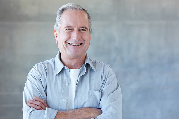Bring on life's next chapter Portrait of a happy retired man standing in his home one senior man only stock pictures, royalty-free photos & images