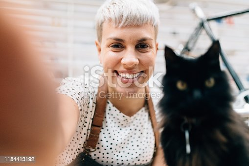 Woman takes a selfie with cat in bicycle shop