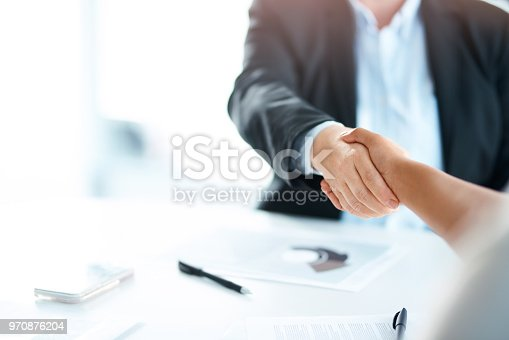 Cropped shot of two businesswomen shaking hands during a meeting in a modern office