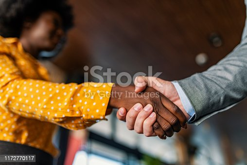 Two multiracial business partners handshaking focus on African-american employee making successful deal. Black female owner boss congratulating Caucasian male candidate with new job career advancement