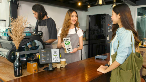 Bring your own cup get discount, Young asian woman barista, waitress introducing zero waste promotion to asia girl customer in coffee shop cafe stock photo