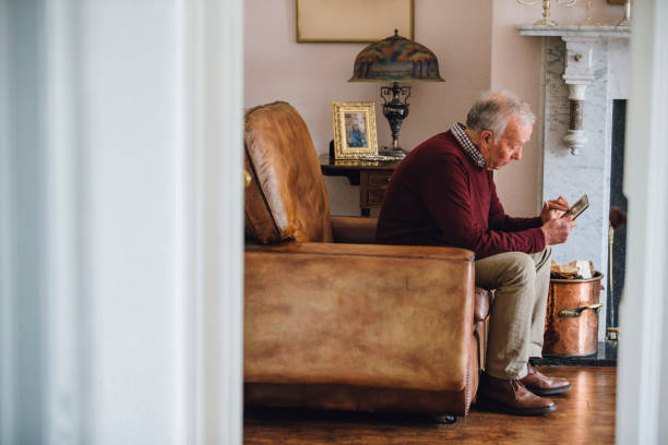 Bringing Back Memories Senior man is sitting in an armchair in the living room of his home, holding and looking at an old photo with a sad expression. mourning stock pictures, royalty-free photos & images