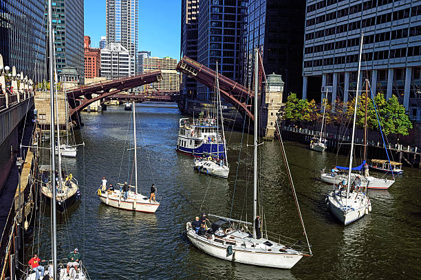 Bringing boats off Lake Michigan for winter Chicago, USA - October 25, 2014: Bringing boats off Lake Michigan for the winter. Boats waiting for bridge openings along the Chicago River in The Loop, downtown Chicago. Adams Street Bridge partly raised. People on boats and spectators looking. bascule bridge stock pictures, royalty-free photos & images