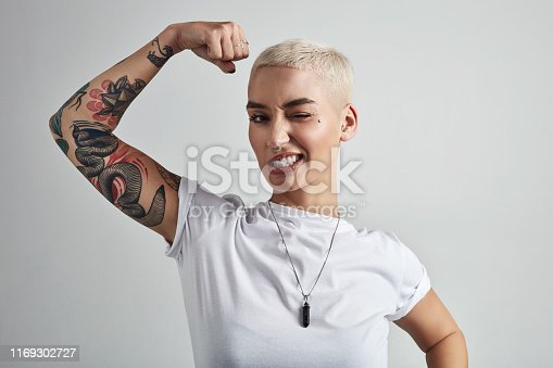 Shot of an attractive young woman flexing her biceps against a grey background