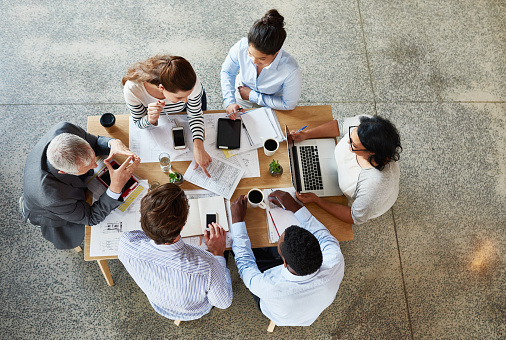 High angle shot of a group of businesspeople working while sitting around in a table