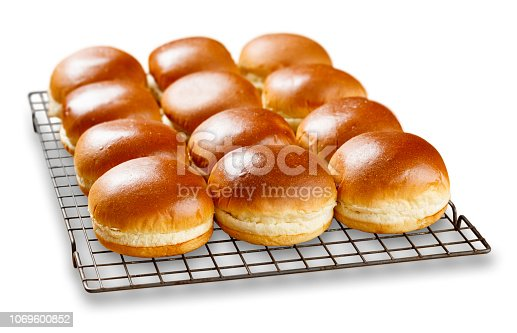 Isolated image of rows of brioch buns cooling on a wire tray.