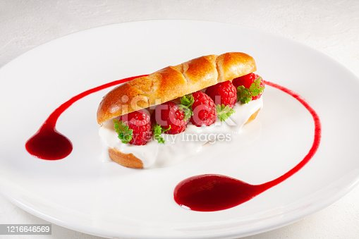 brioche with yogurt and fresh raspberries on a white plate