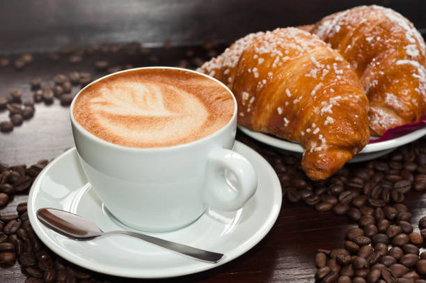 Brioches with cappuccino cappuccino with Brioches and coffee beans croissant stock pictures, royalty-free photos & images