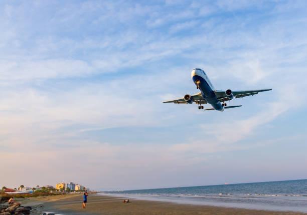 british airways boeing 767 über mckenzie strand vor der landung am flughafen larnaca von menschen am strand fotografiert - b767 stock-fotos und bilder