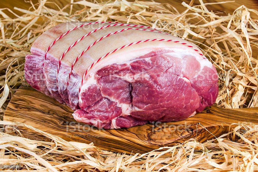 British Boneless Pork Shoulder on cutting board and straw stock photo