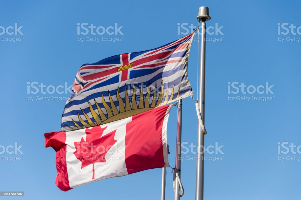 British Columbia flag waving over blue sky in Vancouver, BC, Canada stock photo