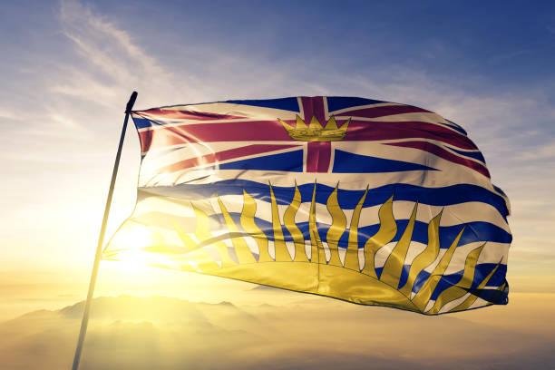 British Columbia province of Canada flag textile cloth fabric waving on the top sunrise mist fog stock photo