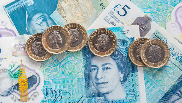 British Currency London, UK: April 20, 2017: The new bi-metallic one pound coin released in 2017 placed on a new polymer Five Pound Note. Both are showing the head of Queen Elizabeth ll. british currency stock pictures, royalty-free photos & images
