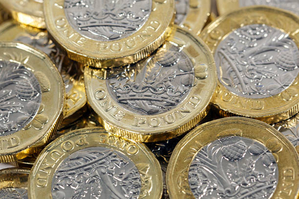 British Currency Scattered one pound coins one pound coin stock pictures, royalty-free photos & images