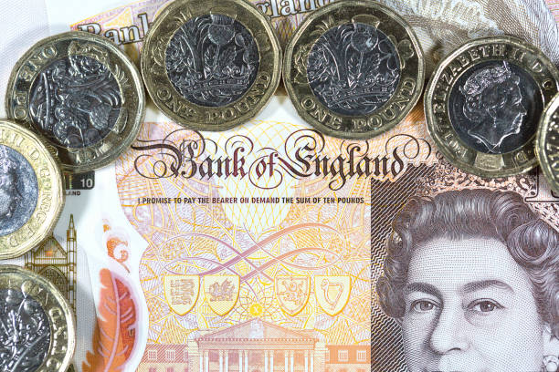 British Currency London, UK: January 03, 2017: British one pound coins with a ten pound note background in a horizontal format. Both the coins and note are a new issue designed to deter counterfeiting. The note is polymer and waterproof ten pound note stock pictures, royalty-free photos & images