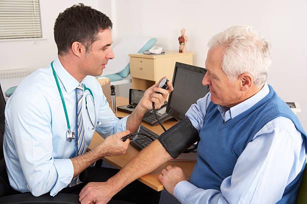 英国医師中の老人男性の血圧計 - 一般開業医 ストックフォトと画像