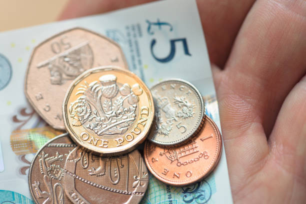 British five pound note and coins stock photo