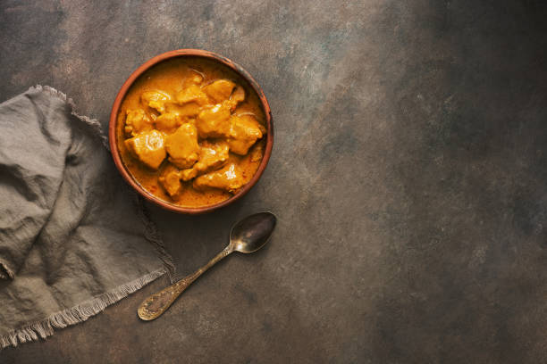 British m Indian food spicy chicken tikka masala on a dark brown rustic background. Top view, copy space. British m Indian food spicy chicken tikka masala on a dark brown rustic background. Top view, copy space garam masala stock pictures, royalty-free photos & images