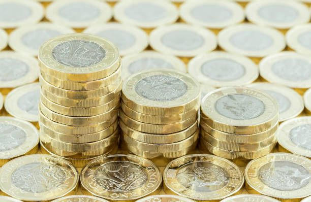 British money, new pound coins in three stacks. stock photo