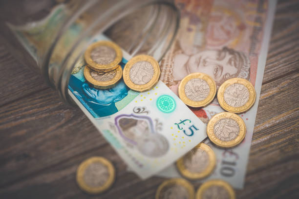 British Money A stock photo of some British Money spilling out of a glass jar on a wooden background. Showing a Five and Ten pound note with the new One Pound coins. british currency stock pictures, royalty-free photos & images
