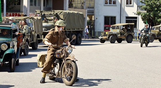 Udine, Italy. May 1, 2021. British soldier on a motorcycle in front of column of Allied military vehicles , during a reenactment of the Second World War in the city.