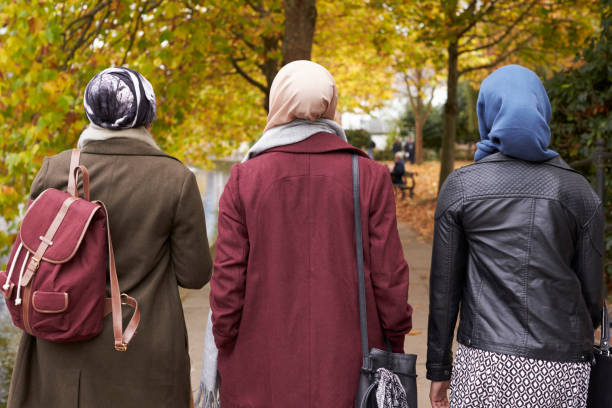 British Muslim Female Friends Walking In Urban Environment British Muslim Female Friends Walking In Urban Environment religious veil stock pictures, royalty-free photos & images
