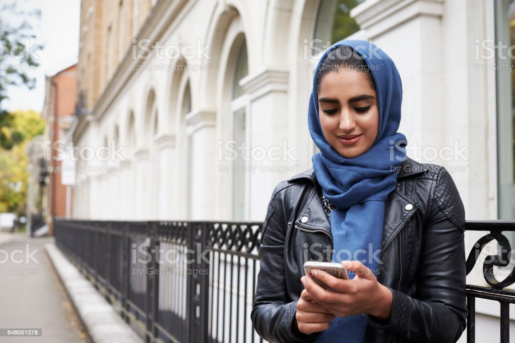 British Muslim Woman Using Mobile Phone In Urban Setting stock photo